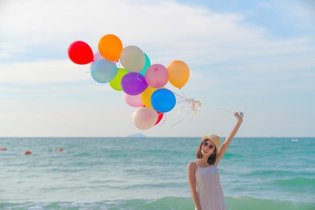 Młoda kobieta z kolorowymi balonami w lato polu