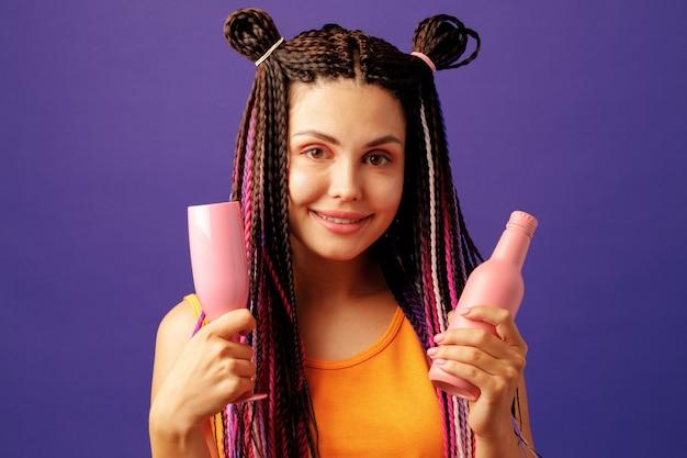 Młoda kobieta z kolorowymi warkoczami afro trzyma butelkę napoju na fioletowym tle