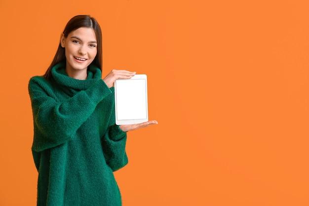 Młoda kobieta z komputerem typu tablet w kolorze