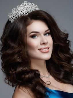 Młoda kobieta z koroną na głowie z błyszczącą wieczorową niebieską sukienką z pięknym uśmiechem