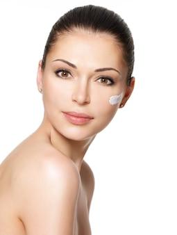 Młoda kobieta z kosmetyczną śmietanką na czystej świeżej twarzy