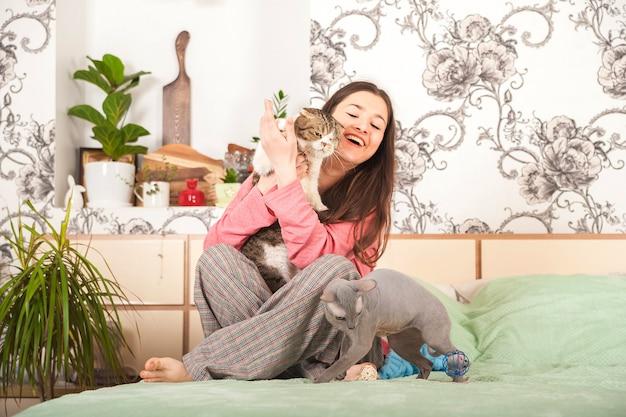 Młoda kobieta z kotami ma zabawę w sypialni. koncepcja pobytu w domu.