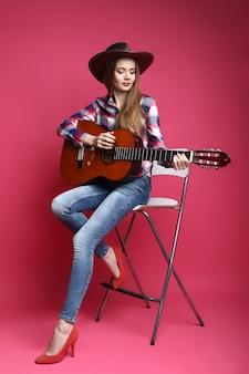 Młoda kobieta z kowbojskim kapeluszem i gitarą na różowym tle
