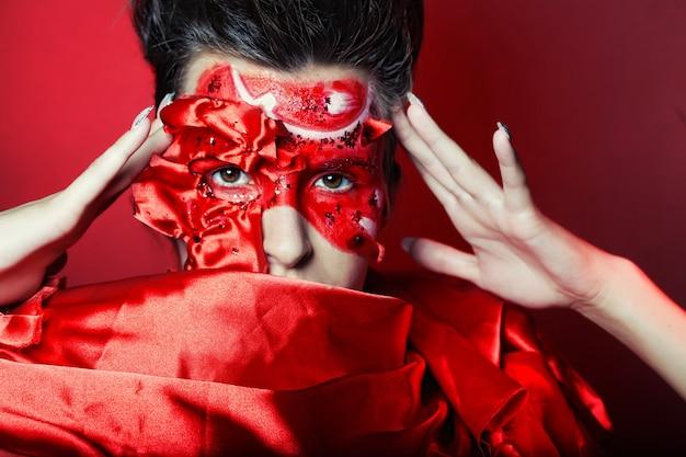 Młoda kobieta z kreatywną czerwoną twarz sztuką