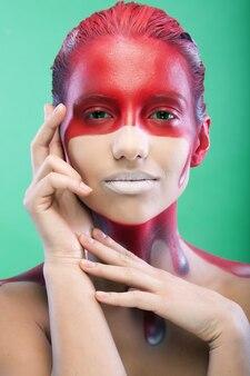 Młoda kobieta z kreatywną sztuką twarzy na zielonym tle