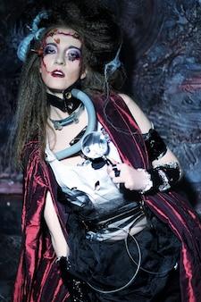 Młoda kobieta z kreatywnym makijażem w czerwonym płaszczu przeciwdeszczowym. motyw halloween. motyw zombie.