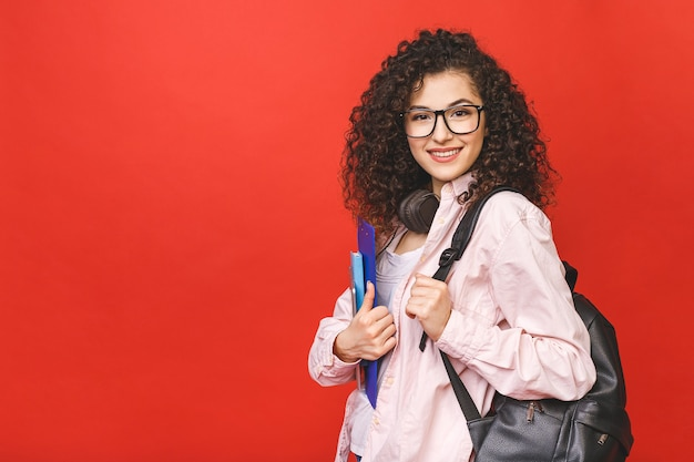 Młoda kobieta z kręconymi włosami brunet z książkami i plecakiem