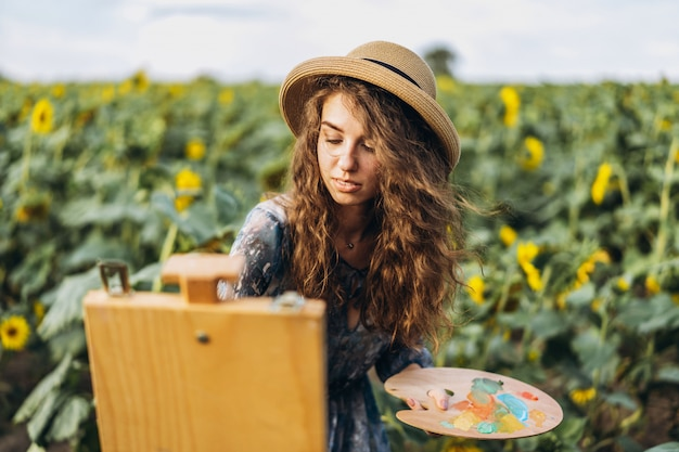 Młoda kobieta z kręconymi włosami i kapeluszem maluje w naturze. kobieta stoi w polu słonecznika w piękny dzień
