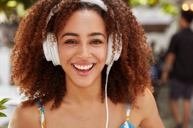 Młoda kobieta z kręconymi włosami i słuchawkami
