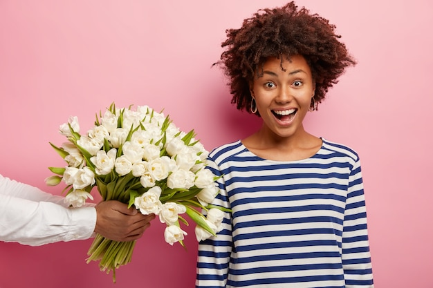 Młoda kobieta z kręconymi włosami otrzymujących bukiet białych kwiatów