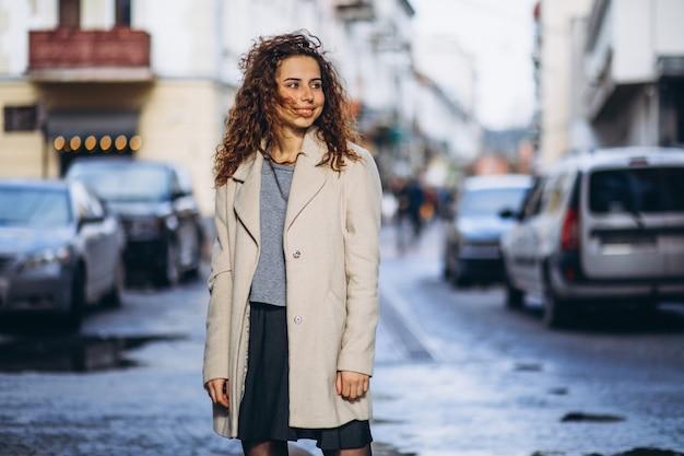 Młoda kobieta z kręconymi włosami poza ulicą