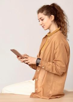 Młoda kobieta z kręconymi włosami przy użyciu telefonu komórkowego