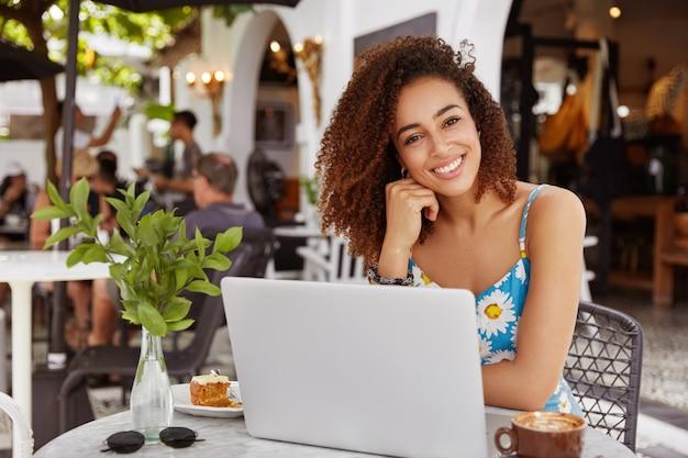 Młoda kobieta z kręconymi włosami siedzi w kawiarni z laptopem