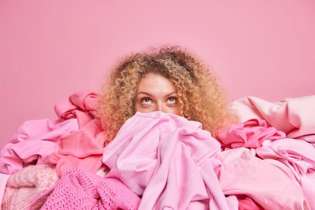 Młoda kobieta z kręconymi włosami skupionymi na górze porządkuje, otoczona stosem ubrań, zbiera ubrania odizolowane na różowej ścianie. poziome ujęcie monochromatyczne. koncepcja rewizji odzieży