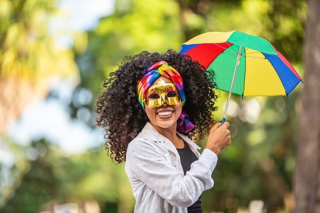Młoda kobieta z kręconymi włosami świętuje brazylijską imprezę karnawałową z parasolem frevo na ulicy.