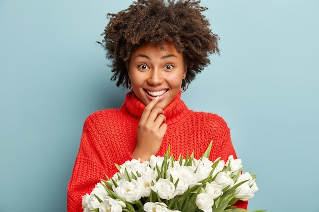 Młoda kobieta z kręconymi włosami trzyma bukiet białych kwiatów