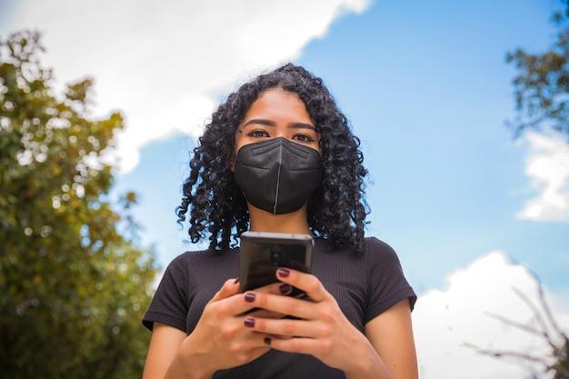 Młoda kobieta z kręconymi włosami używa swojego telefonu, ma czarną maskę na twarzy