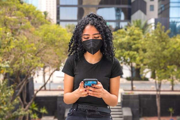 Młoda kobieta z kręconymi włosami używa swojego telefonu, siedzi i ma czarną maskę