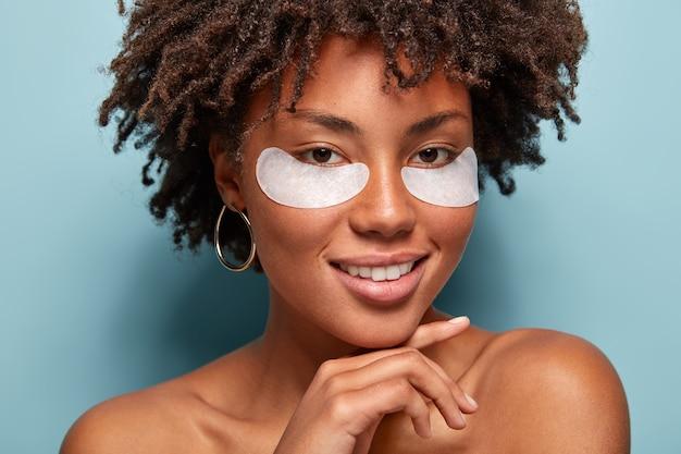 Młoda kobieta z kręconymi włosami z opaskami na oku