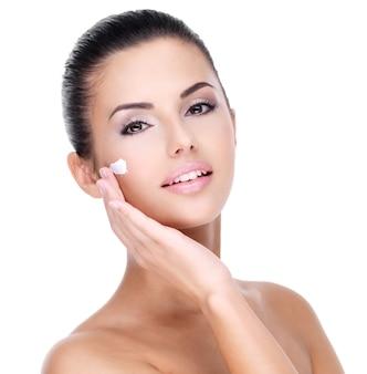 Młoda kobieta z kremem kosmetycznym na całkiem świeżej twarzy - na białym tle