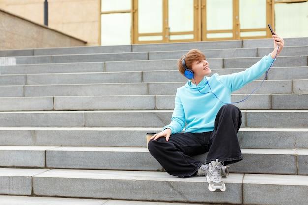 Młoda kobieta z krótką fryzurą w niebieskich słuchawkach robi sobie selfie lub streamuje online, siedząc...