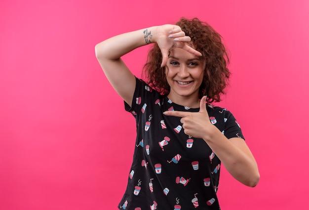 Młoda kobieta z krótkimi kręconymi włosami robiąc ramkę z palcami patrząc przez tę ramkę uśmiechając się radośnie stojąc na różowej ścianie