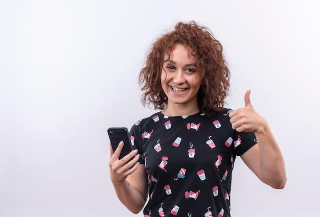 Młoda kobieta z krótkimi kręconymi włosami trzyma smartfona, patrząc uśmiechnięty radośnie pokazując kciuki stojąc na białej ścianie