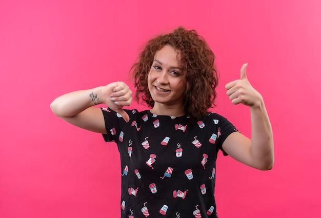 Młoda kobieta z krótkimi kręconymi włosami, uśmiechając się, pokazując kciuki w górę iw dół stojącej nad różową ścianą