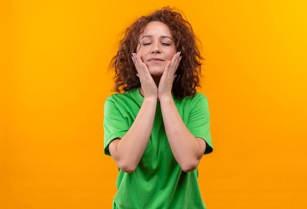 Młoda kobieta z krótkimi kręconymi włosami w zielonej koszulce dotykając jej twarzy rękami czując pozytywne emocje stojąc na pomarańczowej ścianie