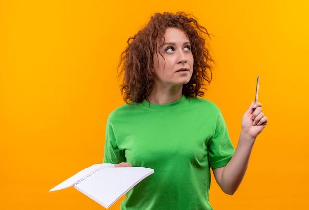 Młoda kobieta z krótkimi kręconymi włosami w zielonej koszulce trzymając notatnik i długopis patrząc w górę myślenia stojącej