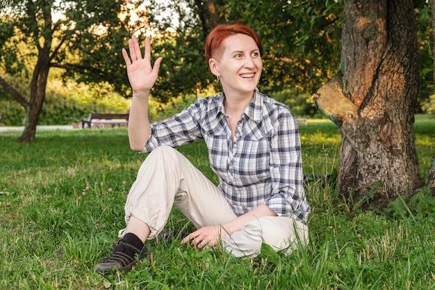 Młoda kobieta z krótkimi rudymi włosami siedzi na trawniku w parku i macha ręką na powitanie