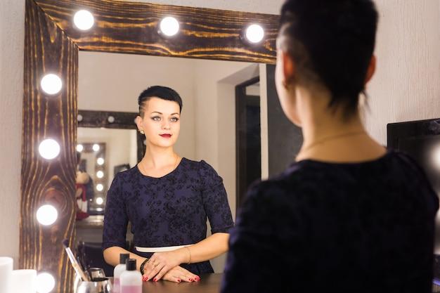 Młoda kobieta z krótkimi włosami, patrząc sobie odbicie w lustrze