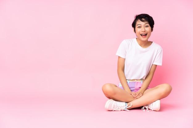 Młoda kobieta z krótkimi włosami siedzi na podłodze na pojedyncze różowe z niespodzianką wyraz twarzy