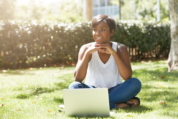 Młoda kobieta z krótkimi włosami siedzi w parku