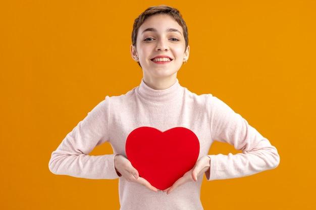 Młoda kobieta z krótkimi włosami trzymając serce wykonane z tektury patrząc na kamery uśmiechnięty wesoło koncepcja walentynki stojący nad pomarańczową ścianą