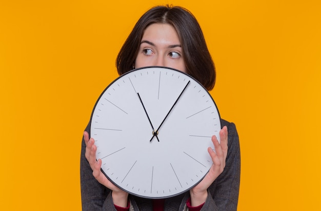 Młoda kobieta z krótkimi włosami, ubrana w szarą kurtkę, trzymając zegar ścienny patrząc na bok zmartwiony stojąc nad pomarańczową ścianą