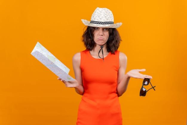 Młoda kobieta z krótkimi włosami w pomarańczowej koszuli w kapeluszu przeciwsłonecznym, trzymając mapę i okulary przeciwsłoneczne, patrząc zaskakująco w kamerę