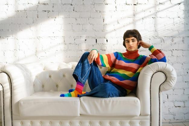 Młoda kobieta z krótkimi włosami w tęczowym swetrze i skarpetkach siedzi na białej kanapie, koncepcji mniejszości seksualnych