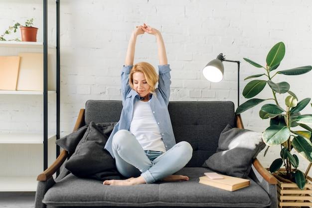 Młoda kobieta z książką wyciągnąć się na przytulnej czarnej kanapie, salon w odcieniach bieli