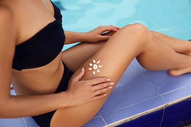 Młoda kobieta z kształtem słońca na nodze, trzymając butelkę kremu do opalania w pobliżu basenu