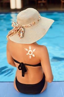 Młoda kobieta z kształtem słońca na ramieniu, trzymając butelkę kremu przeciwsłonecznego