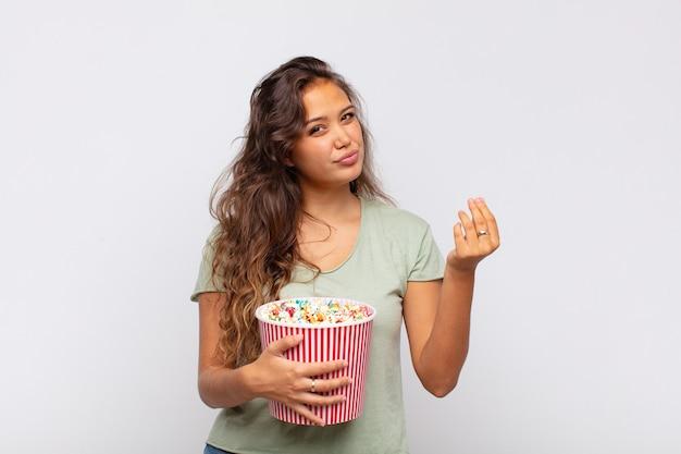 Młoda kobieta z kubełkiem pop conrs robi gest kaprysu lub pieniędzy i każe spłacić długi!