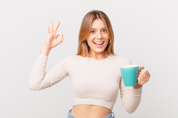 Młoda kobieta z kubkiem kawy czuje się szczęśliwa, pokazując aprobatę dobrym gestem