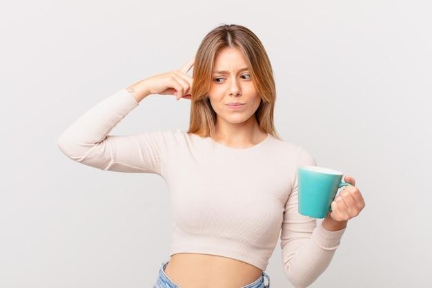 Młoda kobieta z kubkiem kawy czuje się zakłopotana i zdezorientowana, drapiąc się po głowie