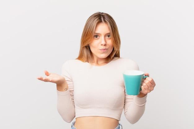 Młoda kobieta z kubkiem kawy czuje się zakłopotana, zdezorientowana i wątpi