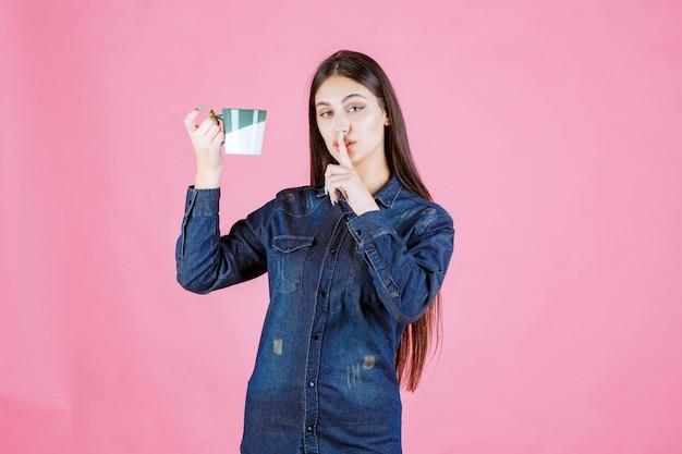 Młoda kobieta z kubkiem kawy robi znak ciszy