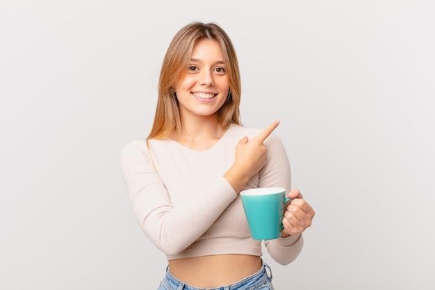 Młoda kobieta z kubkiem kawy uśmiecha się radośnie, czuje się szczęśliwa i wskazuje na bok
