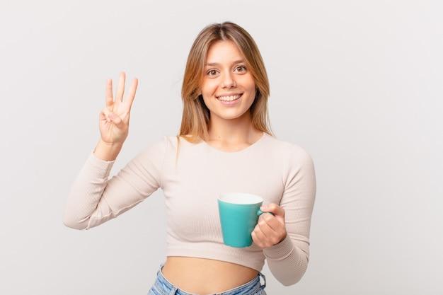 Młoda kobieta z kubkiem kawy uśmiechnięta i wyglądająca przyjaźnie, pokazująca numer trzy