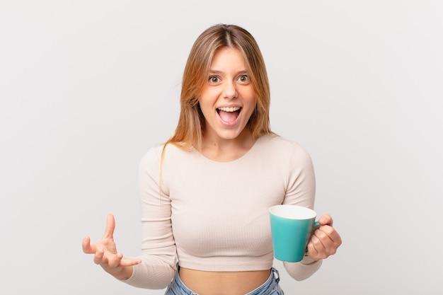 Młoda kobieta z kubkiem kawy wygląda na złą, zirytowaną i sfrustrowaną