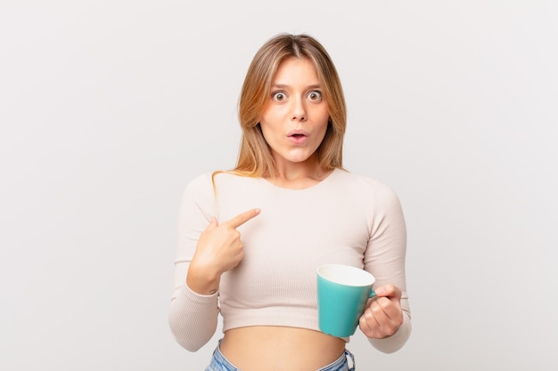 Młoda kobieta z kubkiem kawy wygląda na zszokowaną i zaskoczoną, z szeroko otwartymi ustami, wskazując na siebie